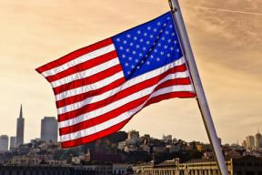 United States flag with San Francisco sklyine in background.
