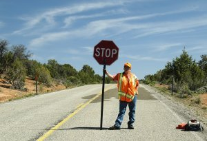 a construction flag man holding a stop sign in the middle of an empty road