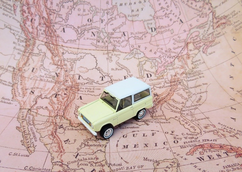 a yellow toy SUV on a map of North America