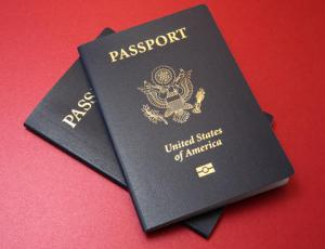 Two United States e-passports on red countertop.