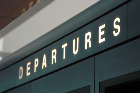 Close-up of airport departures sign.