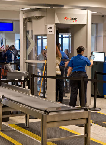 Airport security operating the ProVision ATD full body scanner.