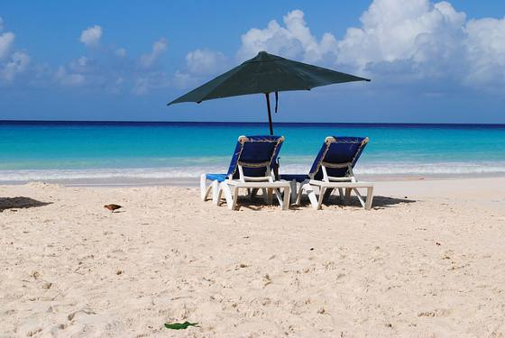Two chairs and umbrella on beautiful Barbados beach.