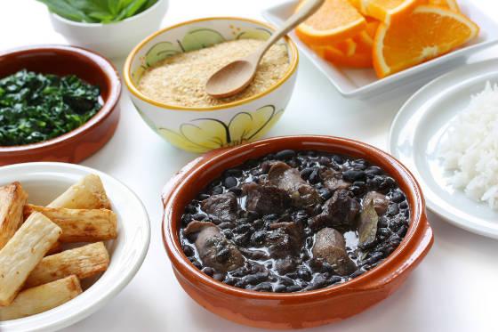 Brazilian food including feijoada, farinha de mandioca, fried macaxeira and white rice.