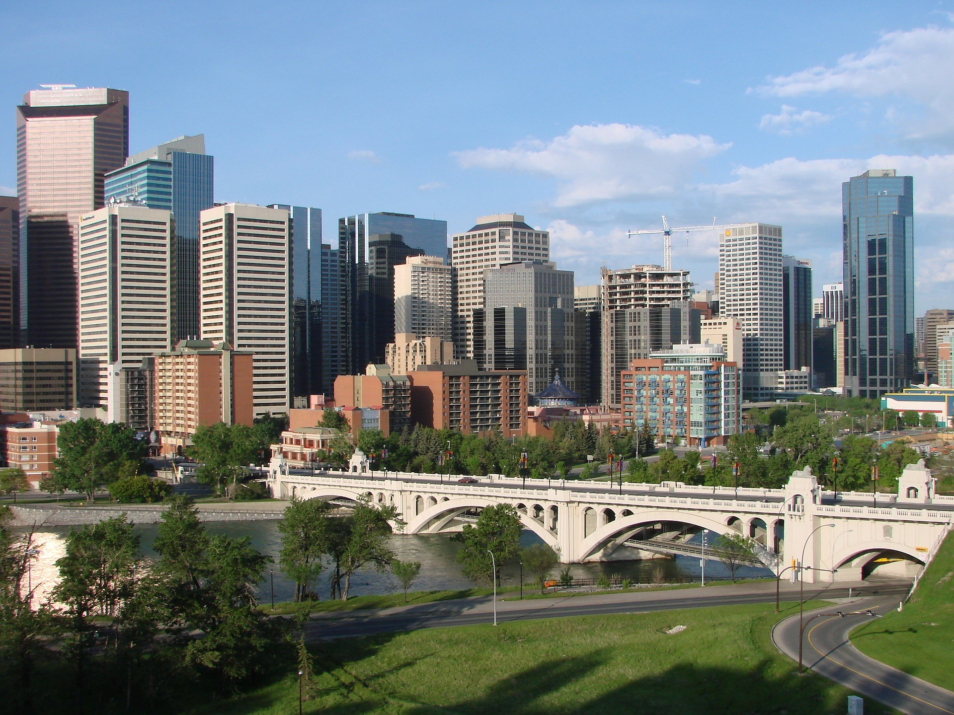 a daytime view of the Calgary, Alberta skyline and a pedestrian bridge over the Bow River