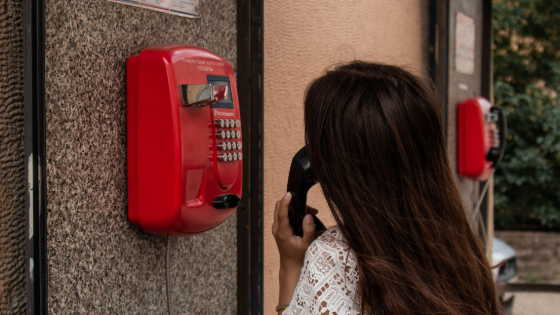 woman calling from a red pay phone