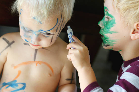 Small girl drawing on her face and face of brother with markers