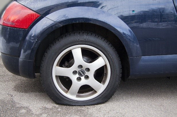 a photograph of a flat tire on a dark blue vehicle