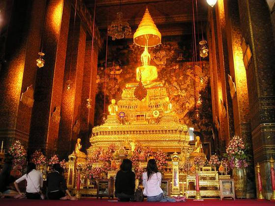 Brightly lit gold alter inside a Buddhist Temple in Bangkok, Thailand