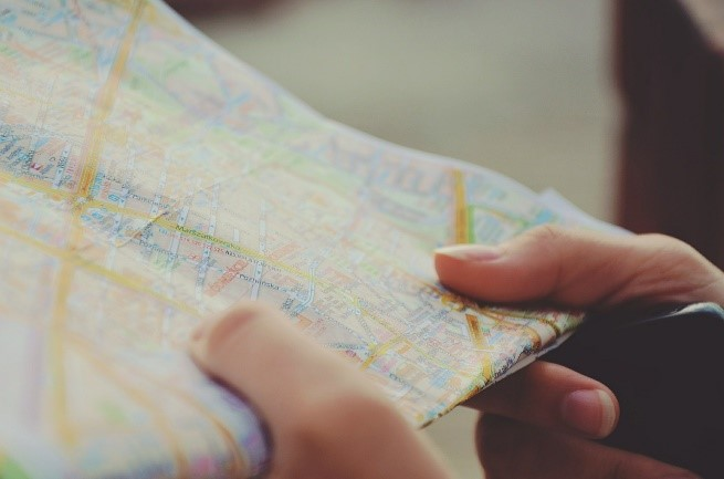 a pair of hands holding a folded map