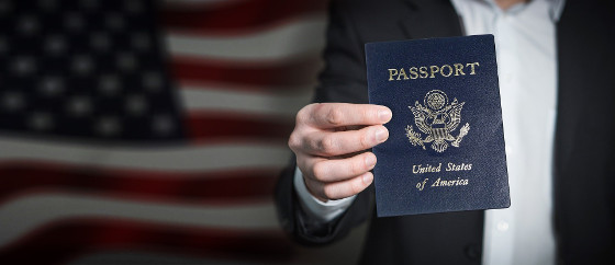 man holding a pasport in front of American flag