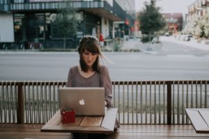 woman working on a laptop at an outdoor cafe