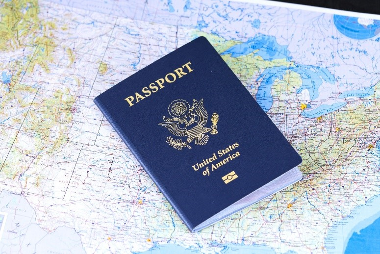 photo of a blue United States Passport on a color map of America