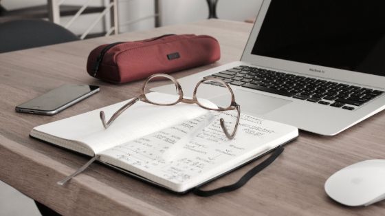 glasses resting on a notebook in front of a laptop
