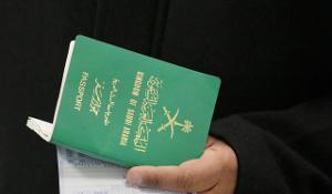 hand holding green saudi passport and document