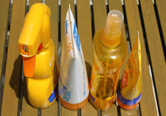 several bottles and tubes of sunscreen on a wooden deck