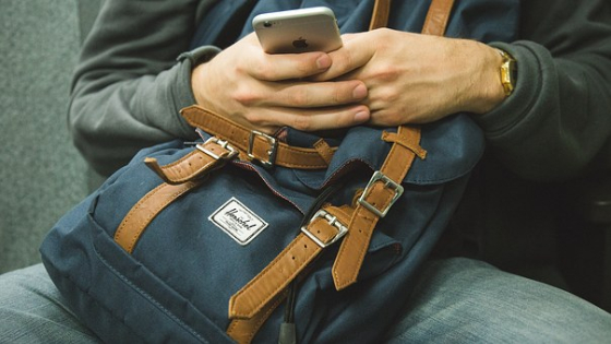 man sitting with bag in lap using phone