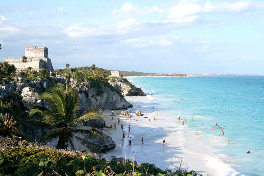 People playing on beach in Tulum Mexico with ruins at top of hill.