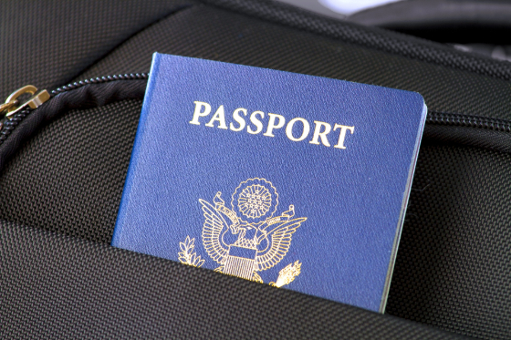 US passport sticking out of a black barryon bag