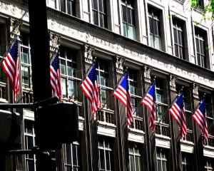 Several USA flags flying on building in NYC.
