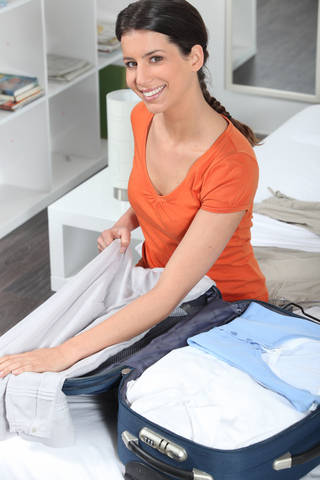 Woman packing a well-organized carryon suitcase.