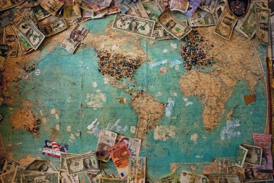 world map with pins and currency
