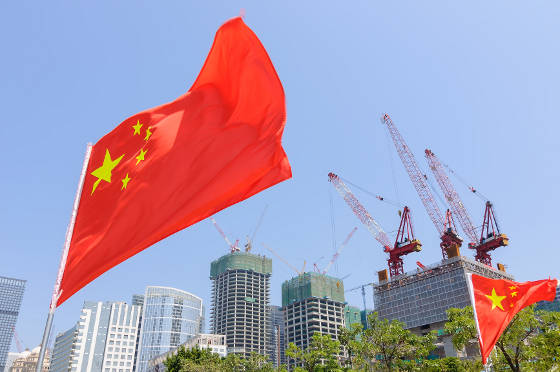 Business buildings with Chinese flags flying in foreground.
