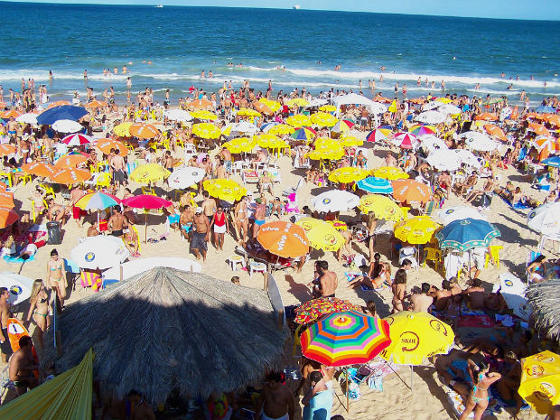 Large crowd on a Brazilian beach during holiday season.