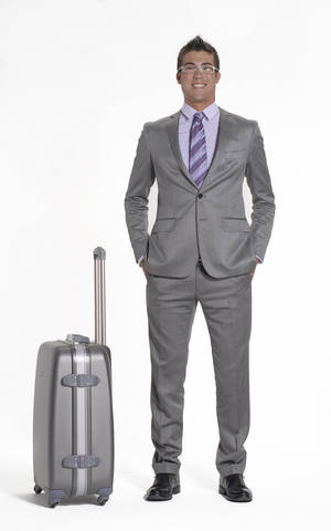 Grey hardside suitcase and businessman in grey suit.