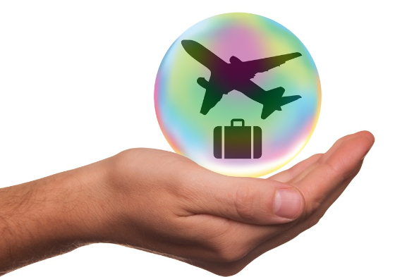 hand holding luggage and plane images in a bubble