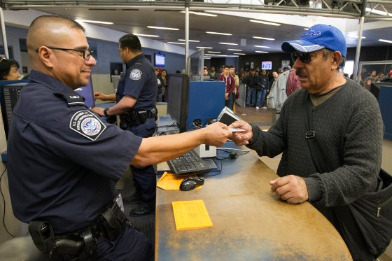 A CBP agent checks a passport at the US Mexico border