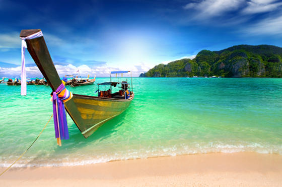 Boat on beach in Thailand with beautiful turquoise water and small island in background.