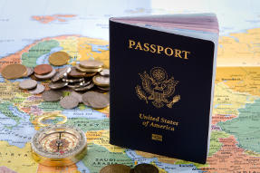 U.S. Passport on Map beside compass and several coins