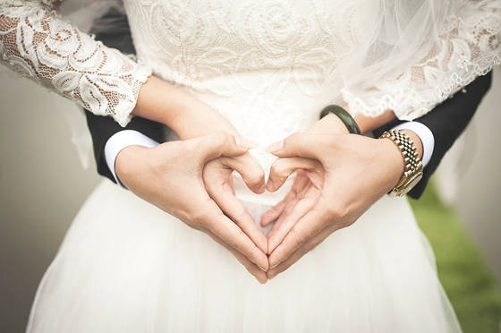Bride and Groom make hearts at wedding