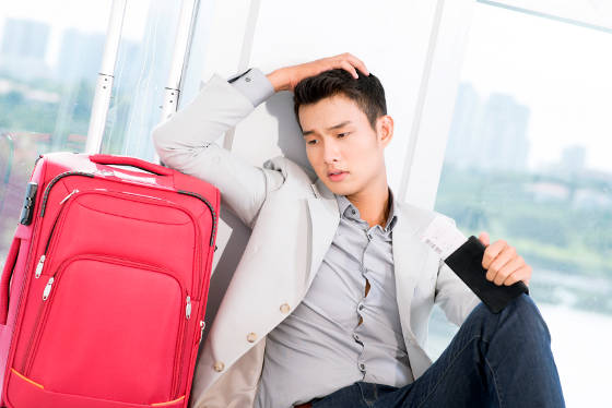 Young man at airport with boarding pass and passport