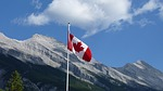 Canadian flag flying with mountains in background.